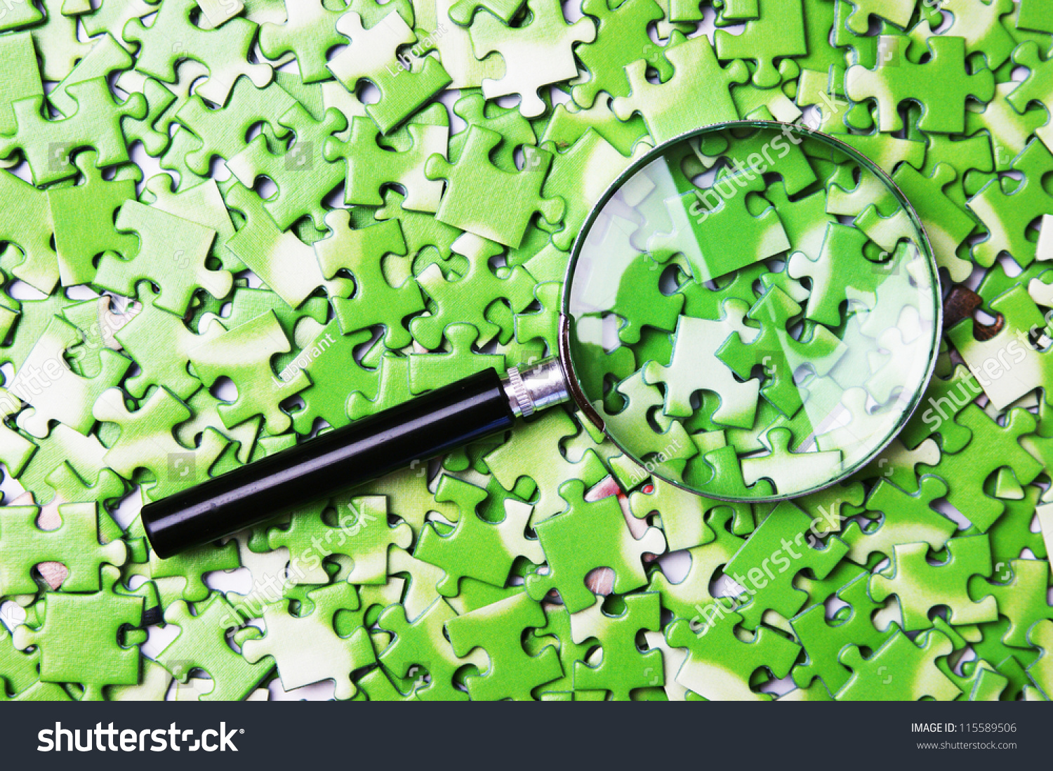 stock-photo-magnifying-glass-on-pile-of-green-puzzle-115589506